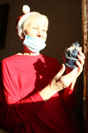Senior woman near the window in the sunny morning with a Santa hat wears a medical mask due to the . Self isolation away from everyone to avoid contagion