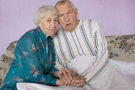 Senior sad elderly couple sitting close together at home - symbol of dementia, empathy and compassion concept