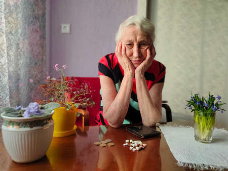Senior woman sitting at home with pills. Poverty concept. All money was spent for pill Standard-Bild