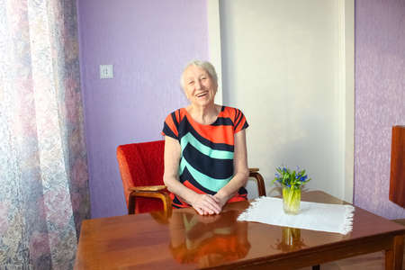 The portrait of a cheerful smiling senior woman over home background