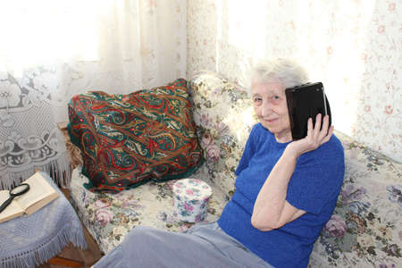 Senior woman with vintage radio at home interior