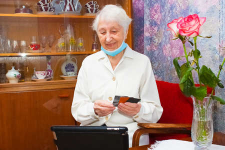 Happy senior woman with face mask making reservation online from home and paying with credit card. Active elderly people interacting with new technologies during quarantine