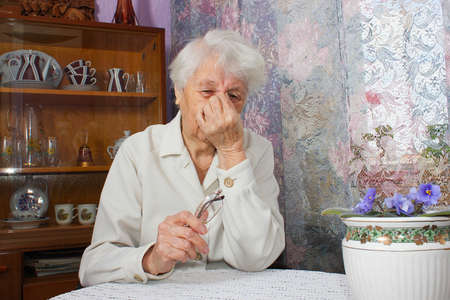 Tired elderly person. Old lonely woman sitting near the window in his house with flowers