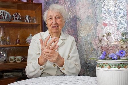 Elderly woman applying moisturizing lotion cream on hand palm, easing aches. Senior old lady experiencing severe arthritis rheumatics pains, massaging, warming up arm.