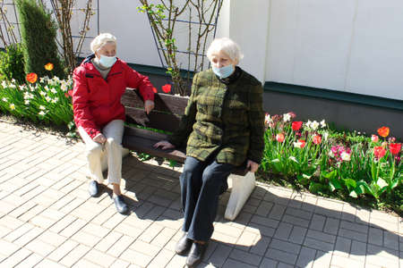 The sad senior women in social distancing sitting at park.  health, safety and pandemic concept