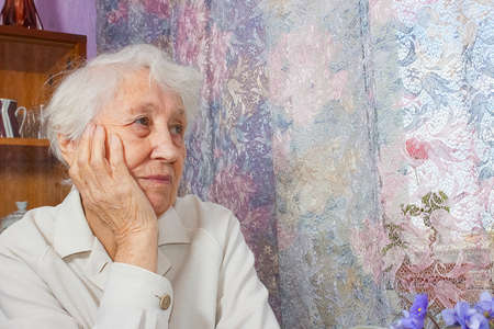 Elderly lonely woman depressed sitting at the table at home