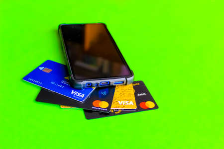Kyiv, Ukraine - April 18, 2021: Credit card and smartphone. Mastercard one of the two biggest credit card companies in the world. Selective focus