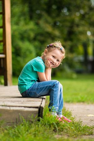 smilling: Cute and smilling little girl in the park in summer day Stock Photo