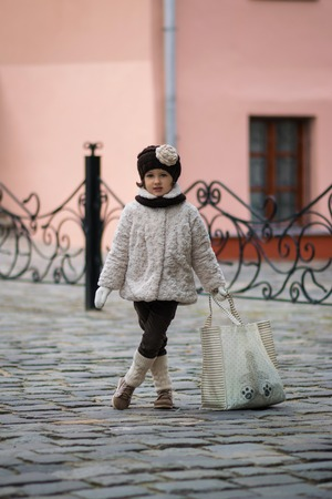 clutch bag: Little fashionable girl in warm clothes in the city
