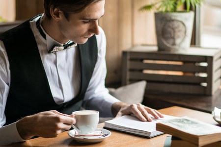 young, successful business man sitting in a cafe with a book and a cup of coffee in a white shirt and tie Stock Photo