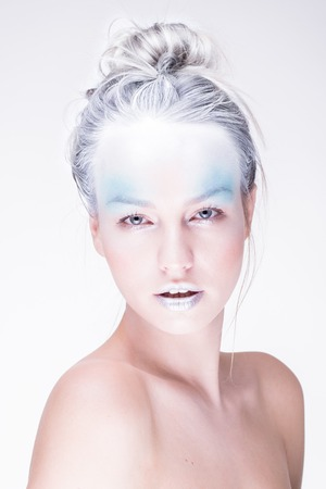 Young winter woman in creative image with silver blue artistic make-up and perfect hairstyle.