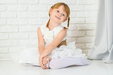 Red haired girl of six years in a white dress