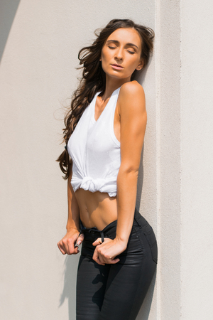Wonderful wet woman in white t-shirt in the city near the stools Stock Photo