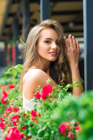 Beautiful girl in the city near retro house with flowers