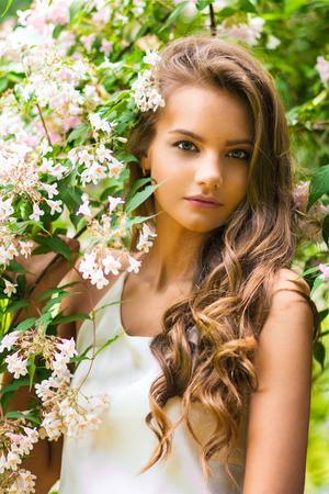 Porträt des schönen Mädchens nahe blühendem Garten der Niederlassungen im Frühjahr
