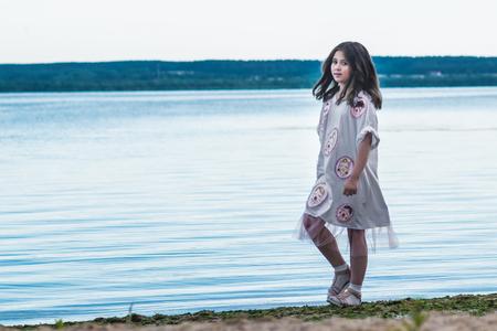 Portrait of little fashionable girl walking on berth near sea Stock Photo