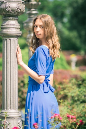 Young woman in dress posing near white columns in park
