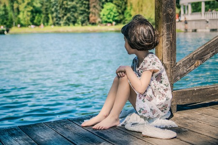 A little young girl is sitting on a wooden pier. Summer day