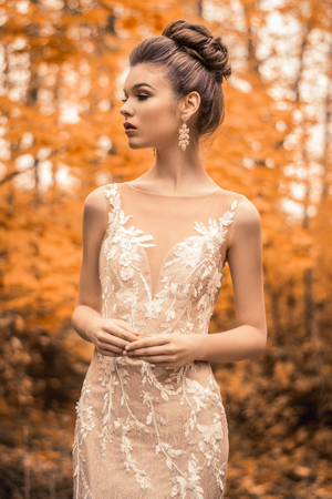 beautiful sensual young brunette bride in long white wedding dress and veil standing in forest 스톡 콘텐츠