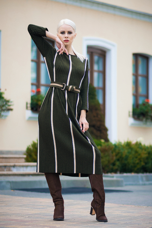 City chic young woman wearing a green dress and boots