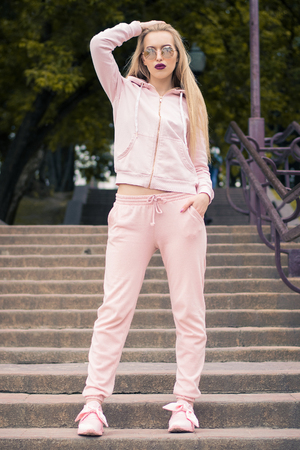tired girl in a sports suit sits on the steps Stock Photo