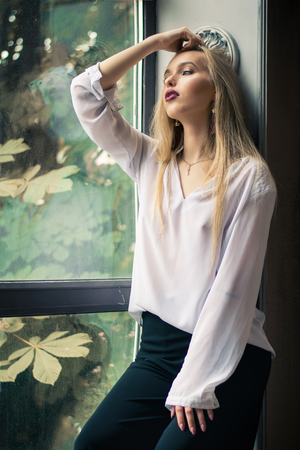 Beautiful fabulous woman in black pants and white shirt. Fashionable and elegant look.
