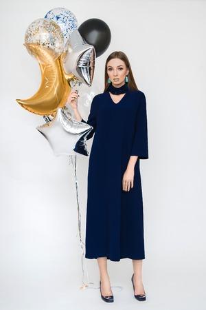 Joyful young woman in luxury dress on heels celebrating new year in studio. Having fun with balloons