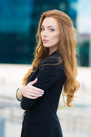 Happy woman standing outdoors in business casual suite against modern mall