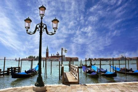 Venice lagoon  Gondolas moored by Saint Mark square with beautiful lamp post and San Giorgio di Maggiore church in the background  Venice, Italy, Europe photo