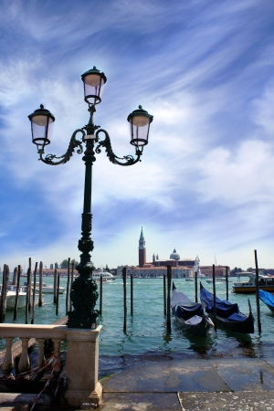 Venice lagoon  Gondolas moored by Saint Mark square with beautiful lamp post and San Giorgio di Maggiore church in the background  Venice, Italy, Europe       photo