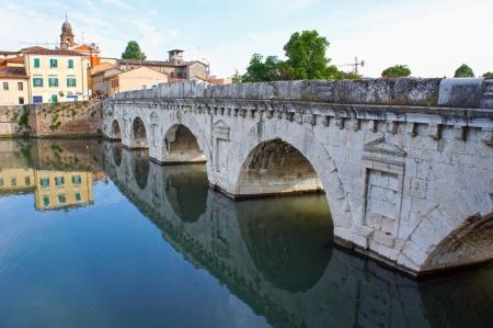 Historical roman Tiberius bridge over river in Rimini, Italy photo
