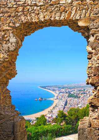 spanish landscapes: View of Spanish beach through a stone door of the St  John Castle of resort town Blanes in summertime  Costa Brava, Catalonia, Spain