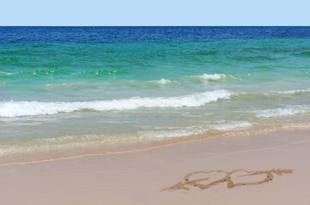 two hearts: Two hearts with an arrow drawn on the sand on beach - love concept