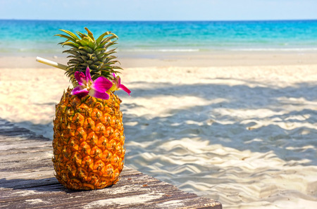 Tropical exotic pineapple cocktail at the beach overlooking the  white sandy beach and blue sea photo