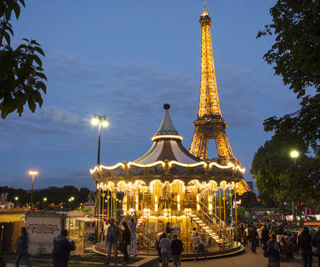 Vintage merry-go-round at night with the illuminated Eiffel Tower in the background on August 21, 2014 in Paris.