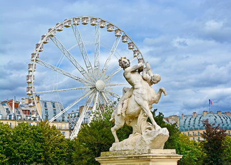 Marble statue and ferriw whell in Tuileries Garden (Jardin des Tuileries). Is  public garden located between Louvre Museum and Place de la Concorde in Paris, France
