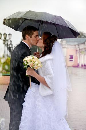 sotto la pioggia: Bella sposi baciare sotto la pioggia. La sposa e lo sposo a piedi sulla strada sotto un ombrello in una giornata piovosa Archivio Fotografico