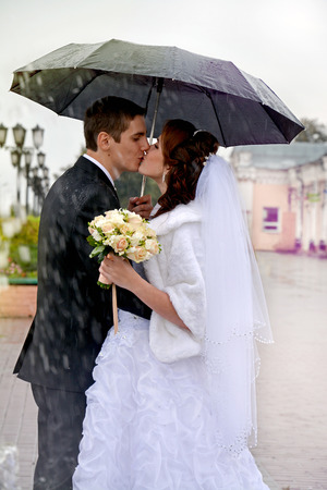 Beautiful wedding couple kissing in the rain. Bride and groom walking on the street under an umbrella on a rainy day Standard-Bild