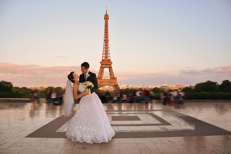 Beautiful wedding couple. Bride and groom in front of the Eiffel Tower in Paris. Retro Style