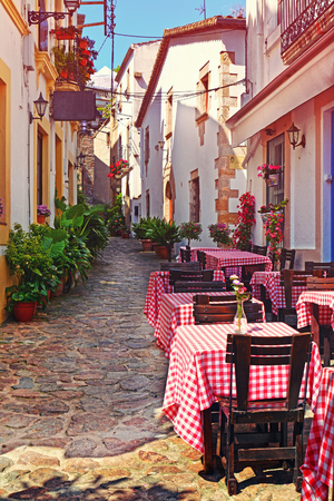 europeans: View of outdoor Cafe on narrow Street in the old European Mediterranean city at sunset