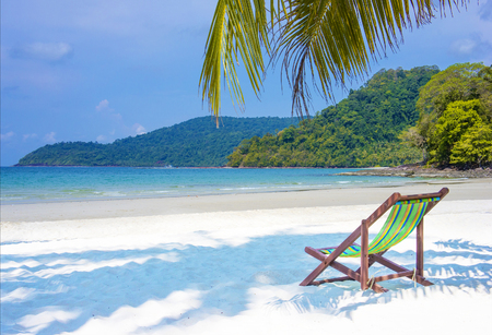Tropical paradise. Seaside view of the tropical island with beach chair on white sand beach. Summer vacation concept background.