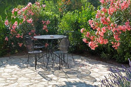 テーブルと椅子は、美しい花の庭園で夏の夜に影を落としてください。 写真素材