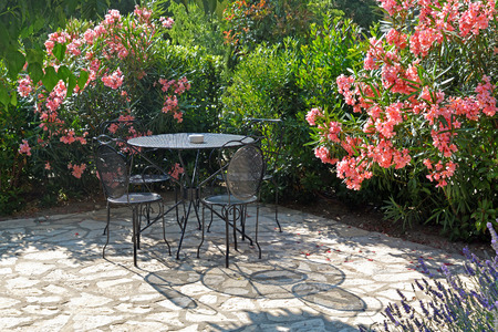 Table and chairs casts a shadow on a summer evening in beautiful flower garden