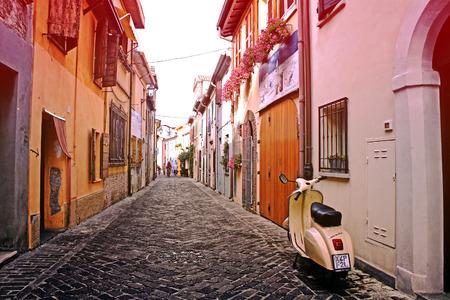 cicla: Rimini, Italia - Junio ??29, 2013: Vespa de la vendimia estacionado en una calle típica de edad estrecha en la puesta del sol en Rimini, Italia. Esta es la forma preferida de viajar en calles estrechas antiguas de Italia Editorial