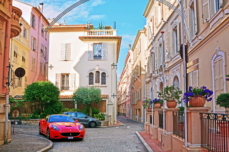 city landscape: MONTE CARLO, MONACO - JUNE 2, 2015:  Red sports car Ferrari on narrow street with old colorful houses in Monaco Ville