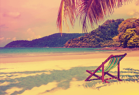 sunset sky: Tropical paradise. Seaside view of the tropical island with beach chair on white sand beach. Summer travel concept background with retro vintage filter.