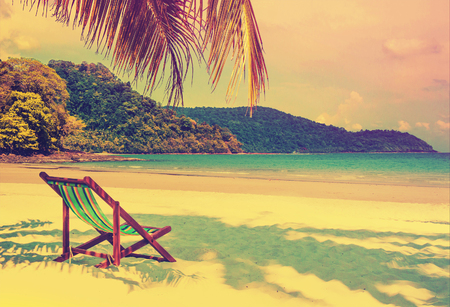 seaside: Tropical paradise. Seaside view of the tropical island with beach chair on white sand beach. Summer travel concept background with retro vintage filter.