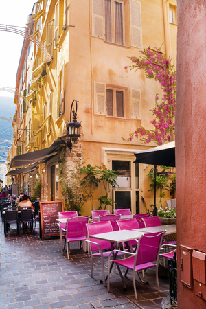 carlo: Narrow street with old color houses and sidewalk cafe with bright pink chairs in Monaco, Monte Carlo. Stock Photo