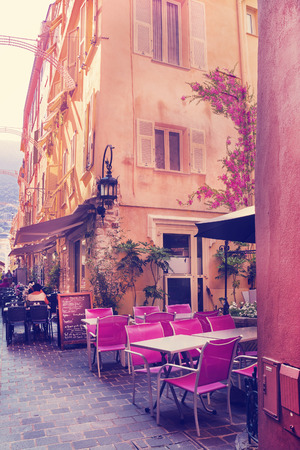 monte carlo: MONTE CARLO, MONACO - JUNE 2, 2015: Narrow street with old color houses and sidewalk cafe with bright pink chairs in Monaco, Monte Carlo.