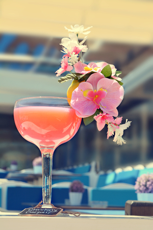 daiquiri: Strawberry Daiquiri Cocktail decorated with pink orchid flowers in a bar on the beach